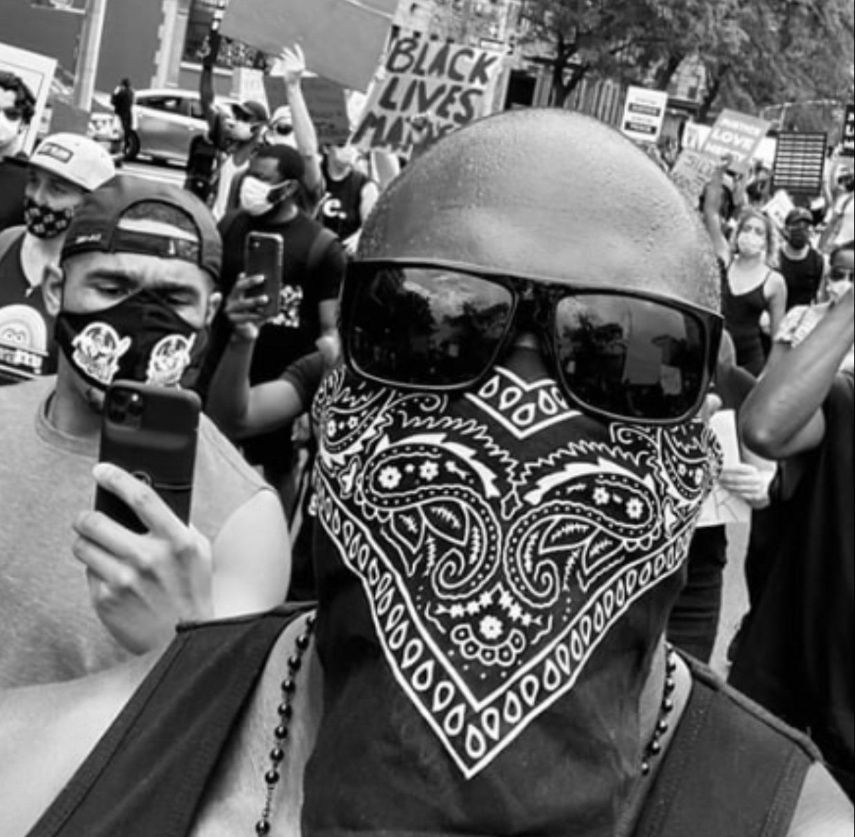 Black and white image of Black man at protest wearing bandana over lower part of face and sunglasses